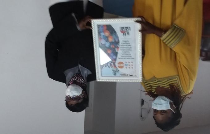 La Coordonnatrice nationale de PPJ, Mme Coura Gaam Diouf remettant à Mme la RR, Cécile Compaoré Z, un tableau magnifiant le travail de UNFPA, le 9/02/2021, Salle Almadie 1 (photo UNFPA Senegal)
