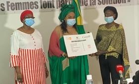 La Ministre de la femme au centre remet à la bénéficiaire à droite la contribution reçue de UNFPA
